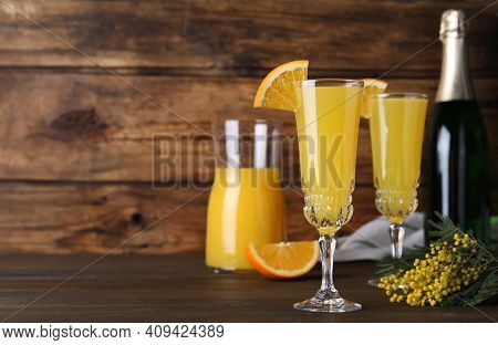 Glasses Of Mimosa Cocktail With Garnish On Wooden Table. Space For Text