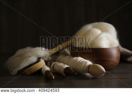 Soft White Wool And Spindles On Wooden Table, Closeup