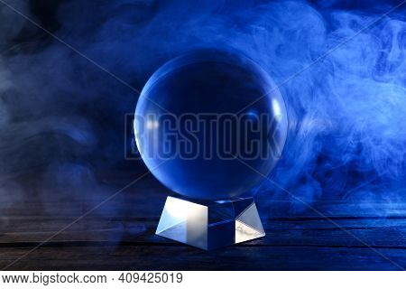 Magic Crystal Ball On Wooden Table And Smoke Against Dark Background. Making Predictions