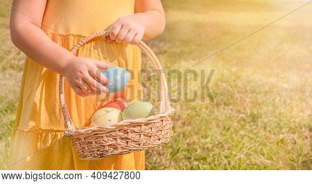 Child With Easter Basket. Girl Pulls Out Easter Egg From Baskets