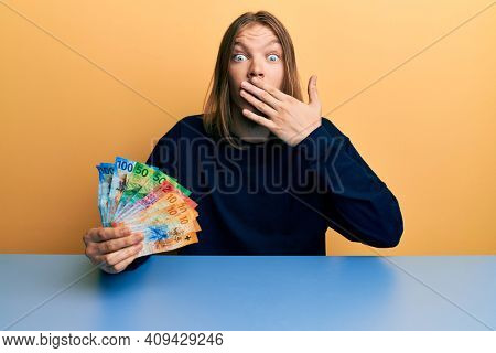 Handsome caucasian man with long hair holding swiss franc banknotes covering mouth with hand, shocked and afraid for mistake. surprised expression