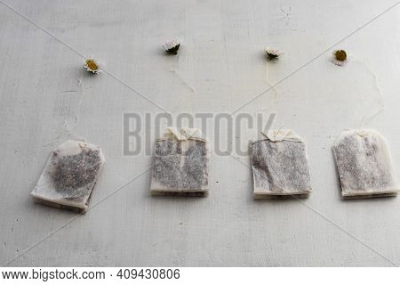 Tea Bags And Chamomile Flowers On White Wooden Background/ Conceptual Image Of Tea Time/ Herbal Cham