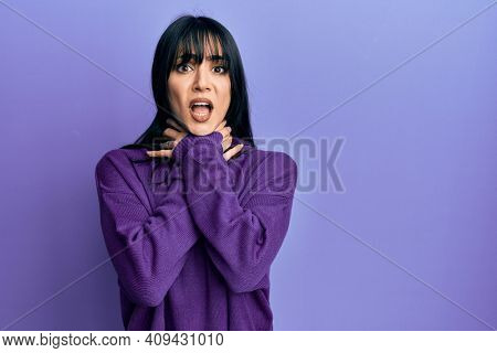 Young brunette woman with bangs wearing turtleneck sweater shouting and suffocate because painful strangle. health problem. asphyxiate and suicide concept.