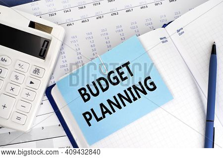 The Label Budget Planning On The Blue Sheet For Notes That Is Attached To The Sheet Of Notepad. A Fi