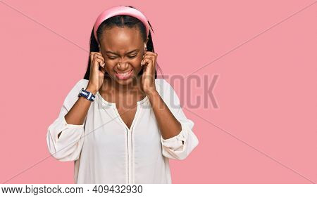 Young black woman wearing casual clothes covering ears with fingers with annoyed expression for the noise of loud music. deaf concept.