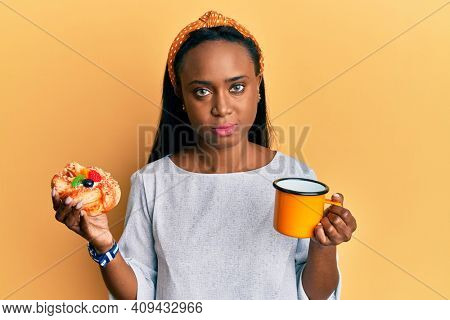 Young african woman drinking coffee and eating pastry relaxed with serious expression on face. simple and natural looking at the camera.