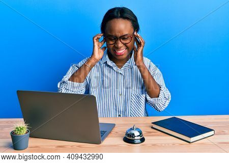 Young african woman working at hotel reception using laptop covering ears with fingers with annoyed expression for the noise of loud music. deaf concept.