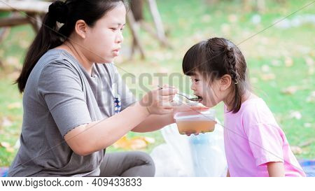 Mom Feeds Her Daughter While Picnicking In A Public Garden. Adorable Girl Opened Her Mouth, Eagerly