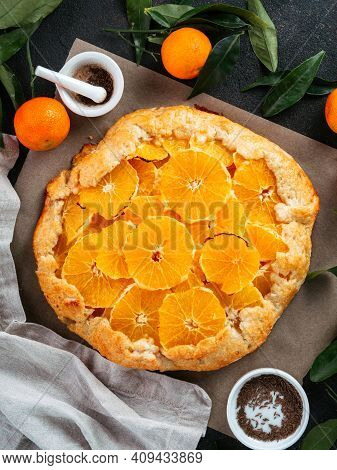 Top View Of Caraway And Orange Tart On Baking Paper Over Black Cement Background. Winter Season And