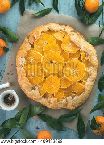 Top View Of Caraway And Orange Tart On Baking Paper Over Gray Wooden Table.winter Season And Christm