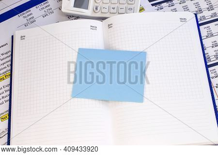 A Blue Blank Sheet Lies On An Open Notebook With Checkered Sheets. A Document With A White Calculato