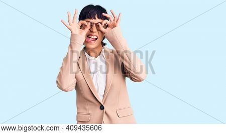 Young brunette woman with short hair wearing business jacket and glasses doing ok gesture like binoculars sticking tongue out, eyes looking through fingers. crazy expression.