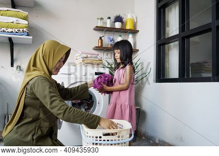 Muslim Asian Mother And Child Girl Little Helper In Laundry Room