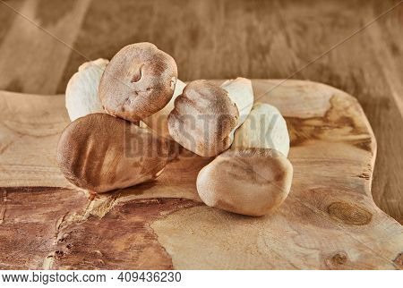 Fresh Mushrooms On An Old Wooden Board On A Wooden Background