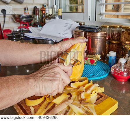 Cooking At Home In The Kitchen According To Recipe From The Internet. Woman Cleans The Dolorit For M