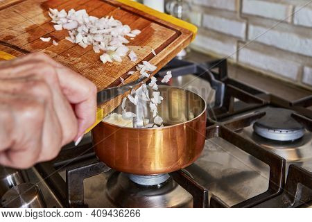 Cooking At Home In The Kitchen According To Recipe From The Internet. Woman Adds Chopped Mini Onions