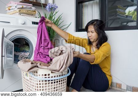 Asian Housewife Doing Some Laundry At Home Feeling Angry