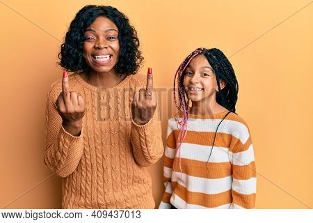 Beautiful african american mother and daughter wearing wool winter sweater showing middle finger doing fuck you bad expression, provocation and rude attitude. screaming excited
