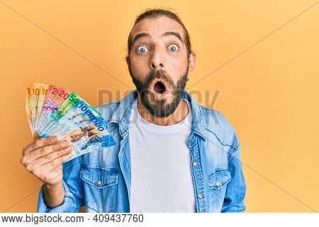 Attractive man with long hair and beard holding swiss franc banknotes scared and amazed with open mouth for surprise, disbelief face