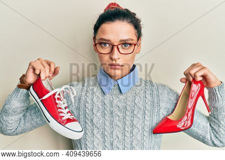 Young caucasian woman choosing high heel shoes and sneakers relaxed with serious expression on face. simple and natural looking at the camera.