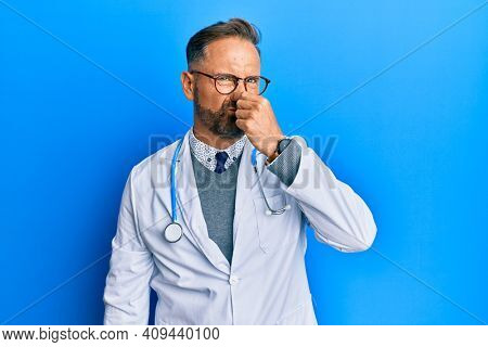 Handsome middle age man wearing doctor uniform and stethoscope smelling something stinky and disgusting, intolerable smell, holding breath with fingers on nose. bad smell
