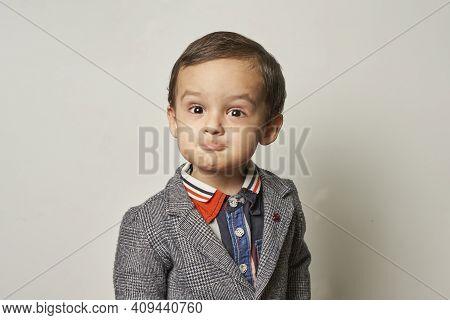 Funny Portrait Of A 2-years-old Boy In A Handmade Elegant Suit. A Kid Boy Making A Funny Foolish Fac