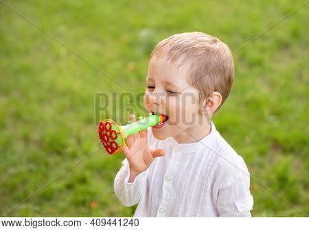 Happy Little Kid Blowing Soap Bubble In School Garden. Caucasian Child Playing With Soap Bubbles. Ch