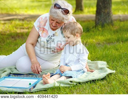 Little Kids And Grandmother. Young Boys And Grandmother Sitting In Sunny Summer Park. Grandma And Gr