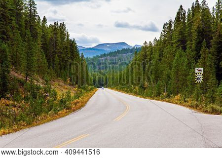 Canadian Rockies. Province of Alberta. Autumn travel to Canada. Cloudy day in the Canadian Rockies. Wide highway runs through dense coniferous forests