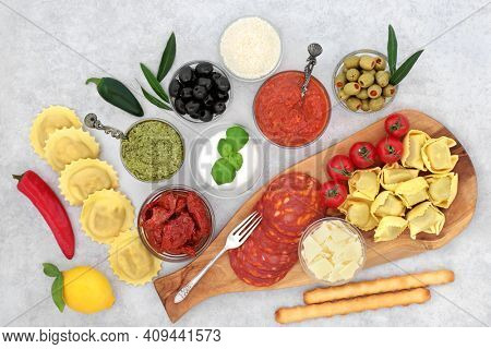 Healthy Italian lunch with a collection of typically Mediterranean health foods. High in protein, antioxidants, anthocyanins, fibre, lycopenes, vitamins and minerals. Flat lay on mottled grey.