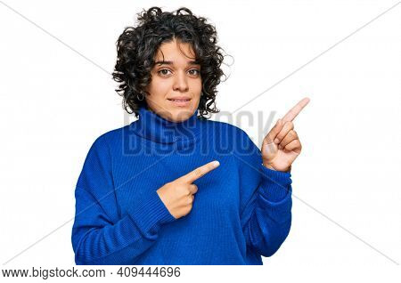 Young hispanic woman with curly hair wearing turtleneck sweater pointing aside worried and nervous with both hands, concerned and surprised expression