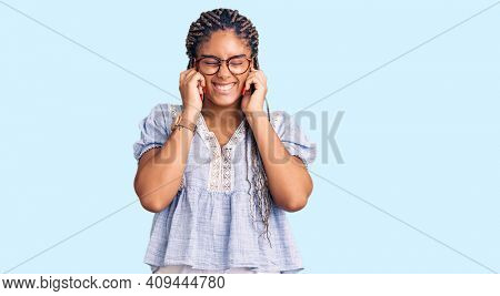 Young african american woman with braids wearing casual summer clothes and glasses covering ears with fingers with annoyed expression for the noise of loud music. deaf concept.
