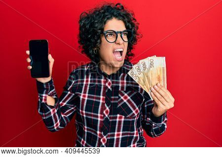 Young hispanic woman with curly hair showing smartphone screen holding 500 norwegian banknotes angry and mad screaming frustrated and furious, shouting with anger looking up.