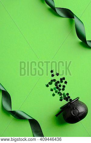 St Patricks Day Minimal Concept. Green Ribbon And Saint Patricks Day Pot With Confetti On Green Back