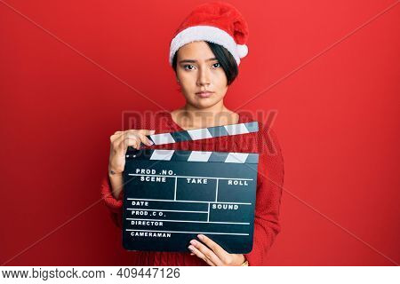 Beautiful young woman with short hair wearing christmas hat holding clapboard relaxed with serious expression on face. simple and natural looking at the camera.