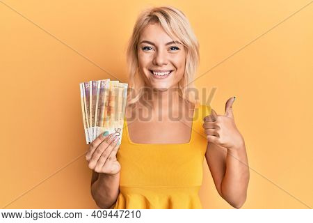Young blonde girl holding norwegian krone banknotes smiling happy and positive, thumb up doing excellent and approval sign