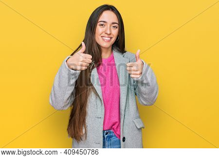 Young hispanic girl wearing business clothes success sign doing positive gesture with hand, thumbs up smiling and happy. cheerful expression and winner gesture.
