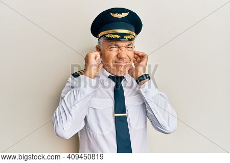 Handsome middle age mature man wearing airplane pilot uniform covering ears with fingers with annoyed expression for the noise of loud music. deaf concept.