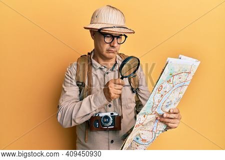 Middle age bald man wearing explorer hat holding magnifying glass on a map relaxed with serious expression on face. simple and natural looking at the camera.