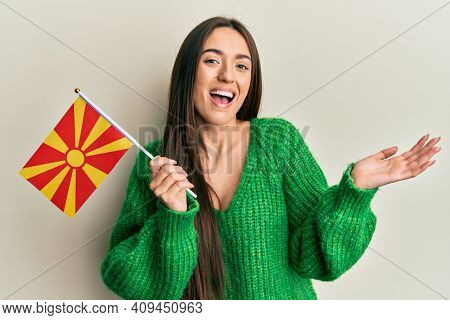 Young hispanic girl holding macedonian flag celebrating achievement with happy smile and winner expression with raised hand