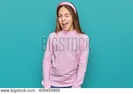 Beautiful brunette little girl wearing casual turtleneck sweater winking looking at the camera with sexy expression, cheerful and happy face.