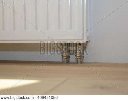A Close-up On A Radiator With Radiator Pipes Coming From The Wooden Floor. Hiding Radiator Pipes Und