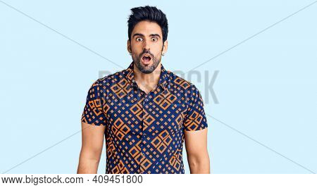 Handsome hispanic man wearing casual clothes scared and amazed with open mouth for surprise, disbelief face