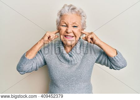 Senior grey-haired woman covering ears with finger smiling and laughing hard out loud because funny crazy joke.