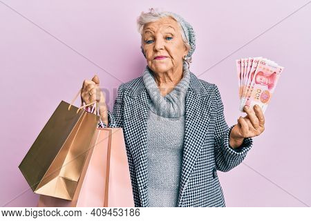Senior grey-haired woman holding shopping bags and israel shekels banknotes relaxed with serious expression on face. simple and natural looking at the camera.