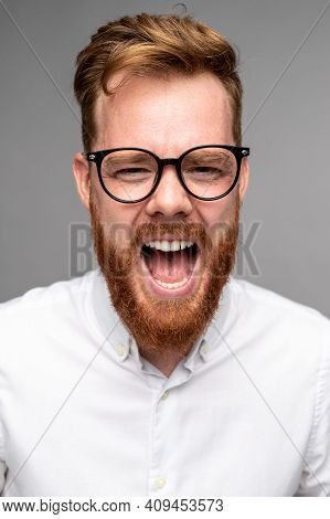 Enraged Bearded Male In Glassed Looking At Camera And Yelling In Anger Against Gray Background