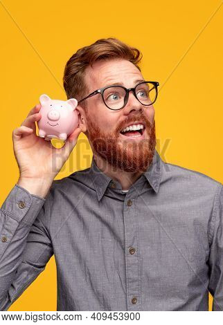 Delighted Bearded Guy Shaking Piggy Bank Near Ear And Smiling While Checking Money Against Yellow Ba