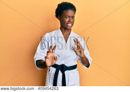 Young african american girl wearing karate kimono and black belt disgusted expression, displeased and fearful doing disgust face because aversion reaction. with hands raised