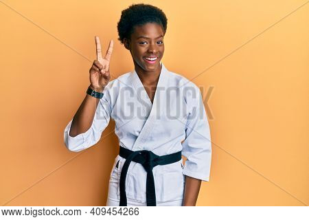 Young african american girl wearing karate kimono and black belt showing and pointing up with fingers number two while smiling confident and happy.