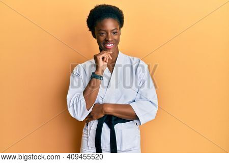 Young african american girl wearing karate kimono and black belt looking confident at the camera with smile with crossed arms and hand raised on chin. thinking positive.